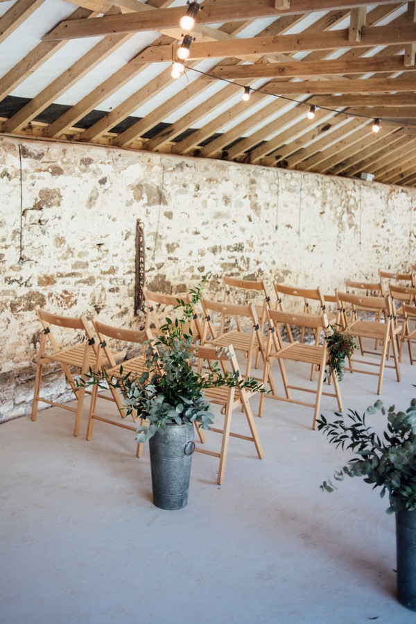 Urns of foliage in front of rustic wedding ceremony chairs