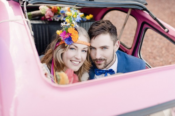 Bride and groom looking out of sunroof of pink car