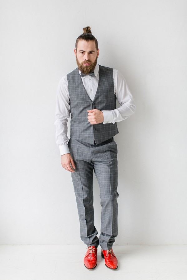 Groom wearing grey check waistcoat and bow tie with red shoes