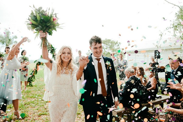 Bride and groom leaving wedding ceremony through shower of confetti