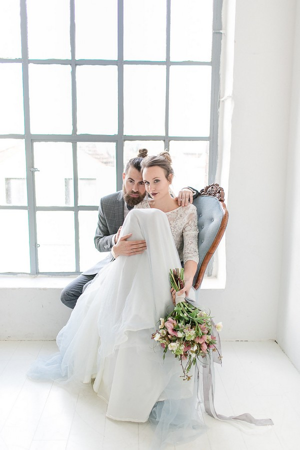 Bride and groom sitting in chair by window