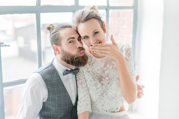 Bride laughing as groom blows kiss
