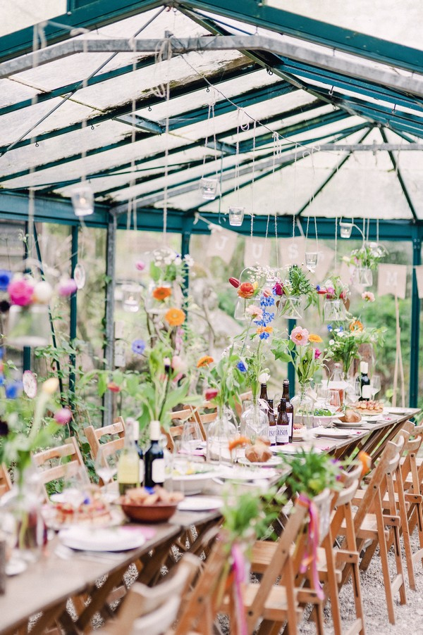 Colourful flowers hanging down over wedding table from string