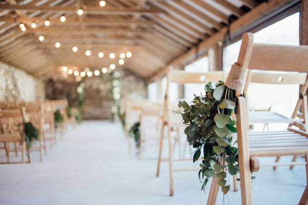 Hand tied bouquet tied to wedding ceremony chair