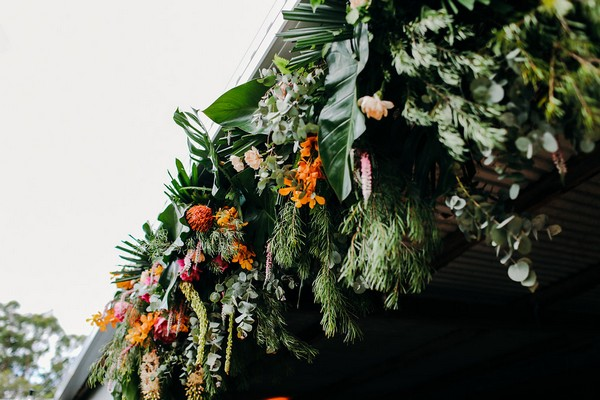 Flowers and foliage hanging from front of wedding barn