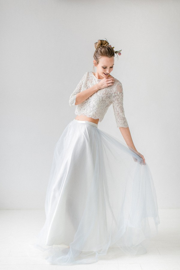 Bride holding out skirt of two-piece wedding dress