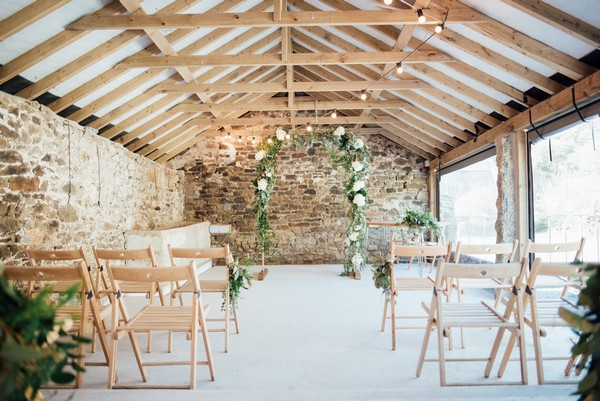 Flower and foliage arch at end of wedding ceremony aisle in The Cowyard Barn at Pengenna Manor
