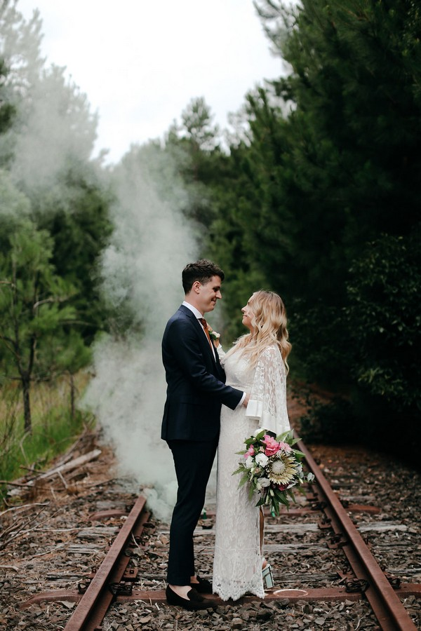 Bride and groom standing on train track