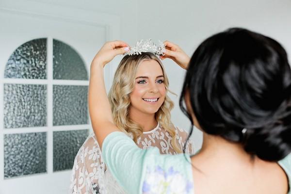 Bridesmaid putting headband on bride's head