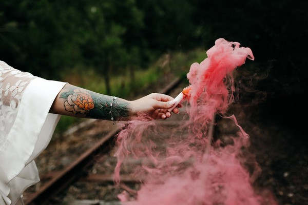 Bride holding out pink smoke bomb