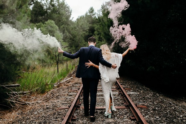 Bride and groom holding smoke bombs walking down train track
