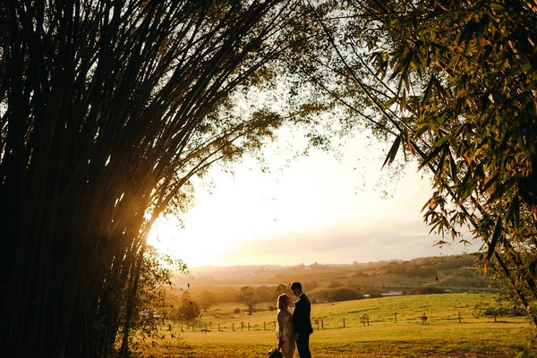 Bride and groom standing in tree clearing