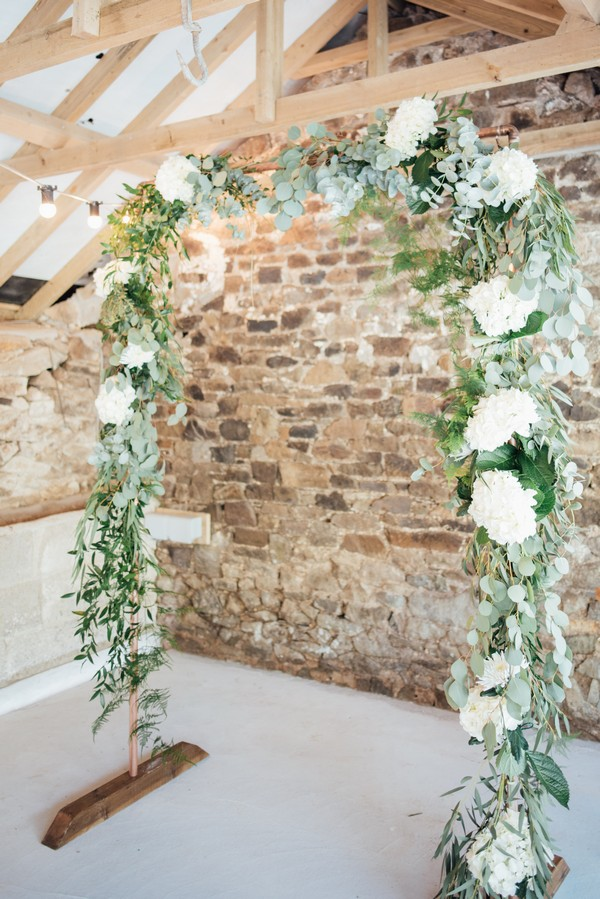 Wedding ceremony arch of white flowers and green foliage
