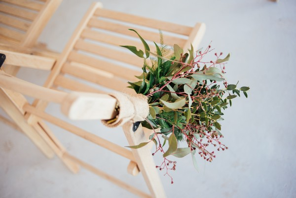 Hand tied bouquet attached to wooden wedding chair