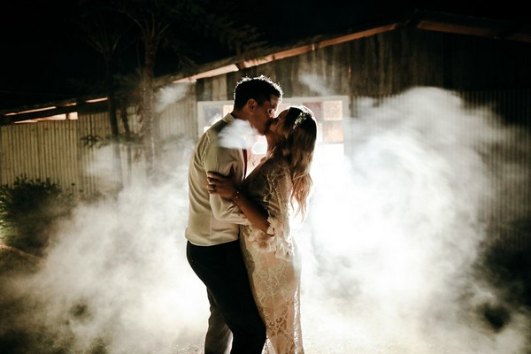 Bride and groom kissing surrounded by smoke