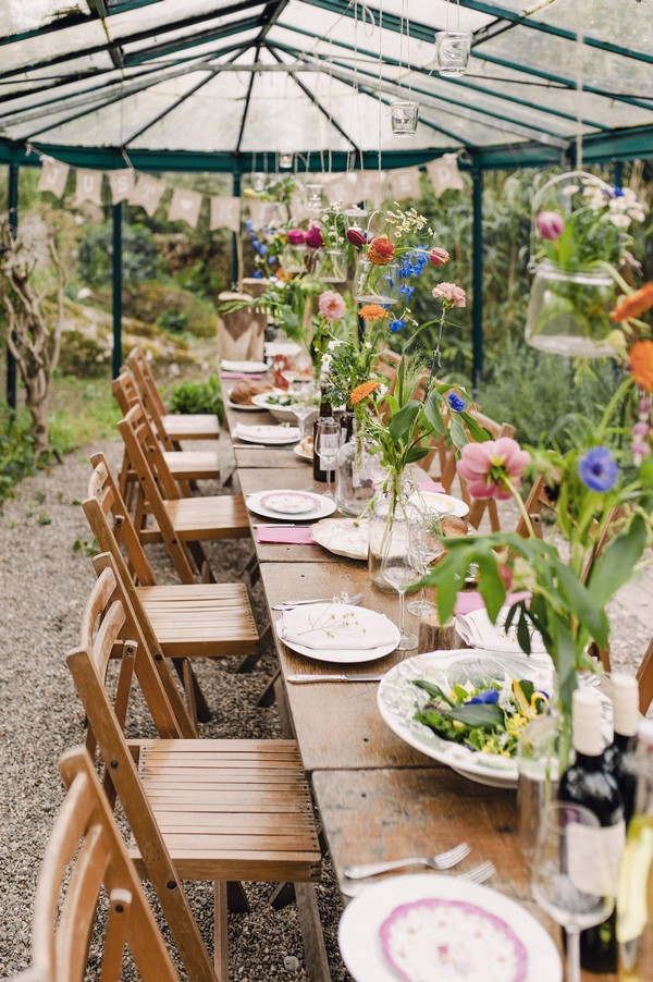 Rustic wedding table with colourful flowers hanging over