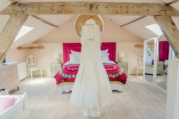 Wedding dress hanging in bedroom of Apple Loft Cottage at Gaynes Park