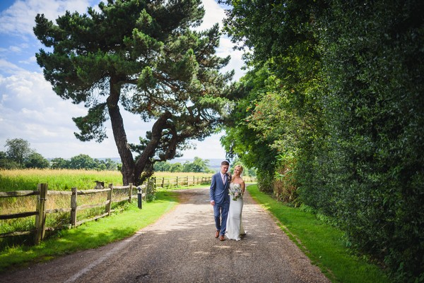 Bride and groom walking in grounds of Gaynes Park