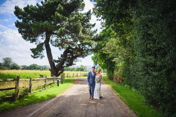 Bride and groom walking in grounds of Gaynes Park