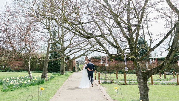 Bride and groom walking in Walled Garden at Gaynes Park