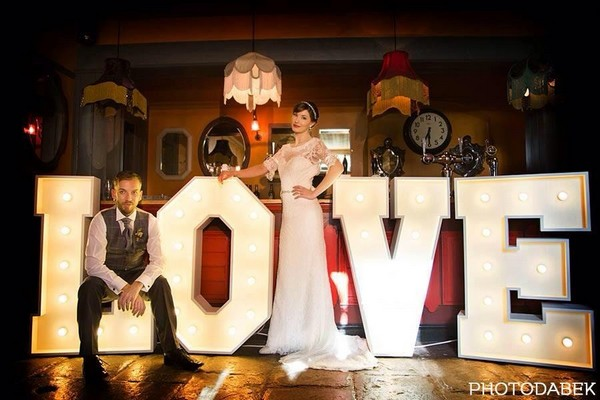 Bride and groom in front of large illuminated LOVE letters