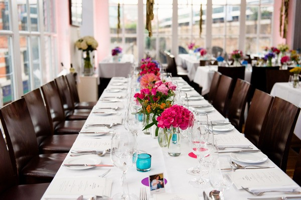 Lond wedding table with colourful wedding table centrepieces