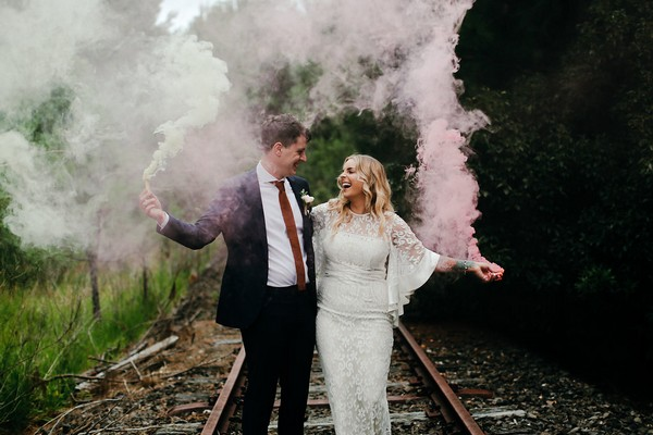 Bride and groom on train track holding smoke bombs