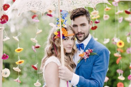 Boho bride and groom under parasol with colourful suspended flower backdrop