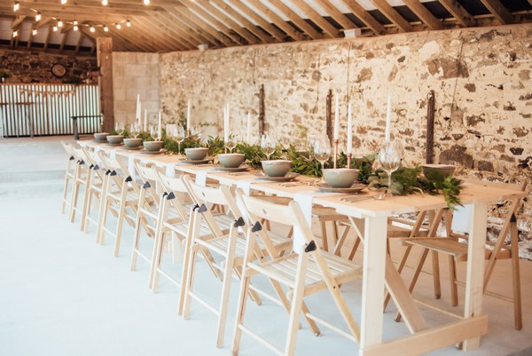 Table with rustic wedding styling in The Cowyard Barn at Pengenna Manor
