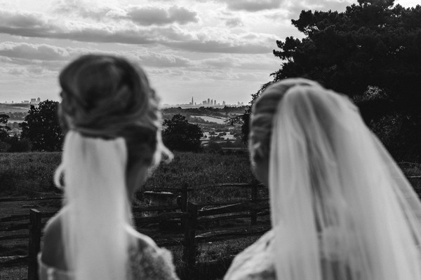 Brides looking at view from Gaynes Park