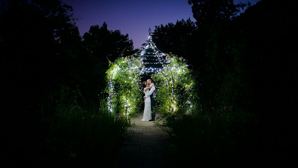 Bride and groom under the Wedding Pavilion at Gaynes Park at night