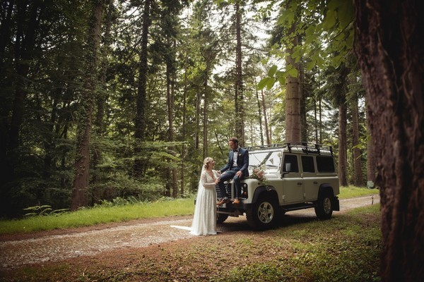 Bride with groom sitting on bonnet of Jeep - Picture by Bethany Lloyd-Clarke Photography