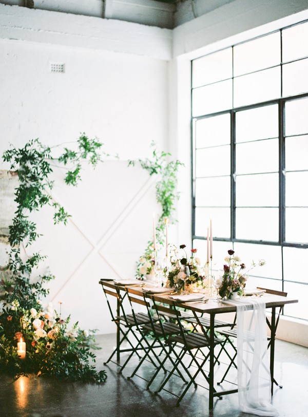 Wedding table and foliage backdrop in urban loft space