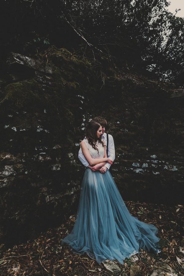 Groom hugging bride wearing blue skirted dress from behind