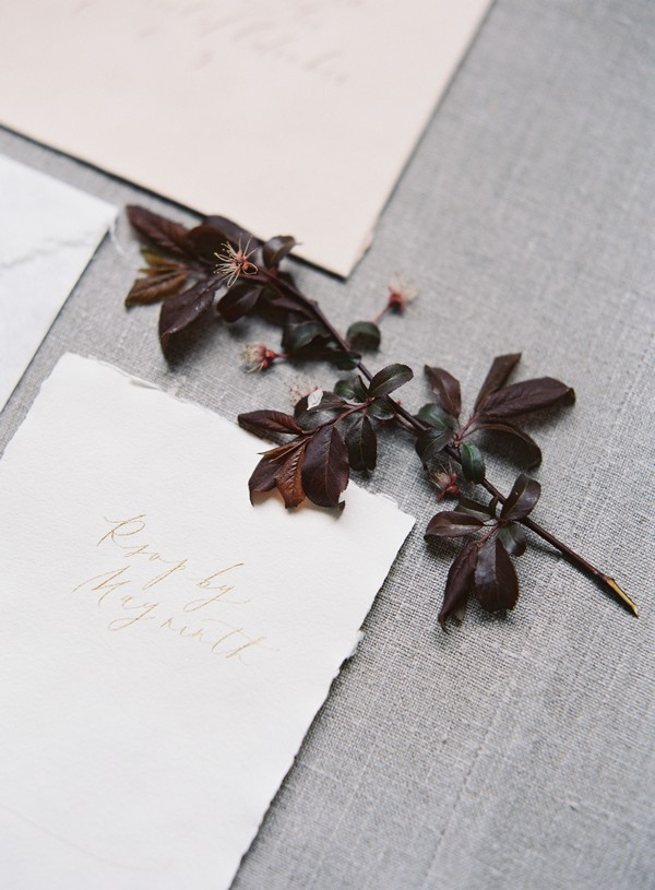 Deep red leaves with wedding stationery