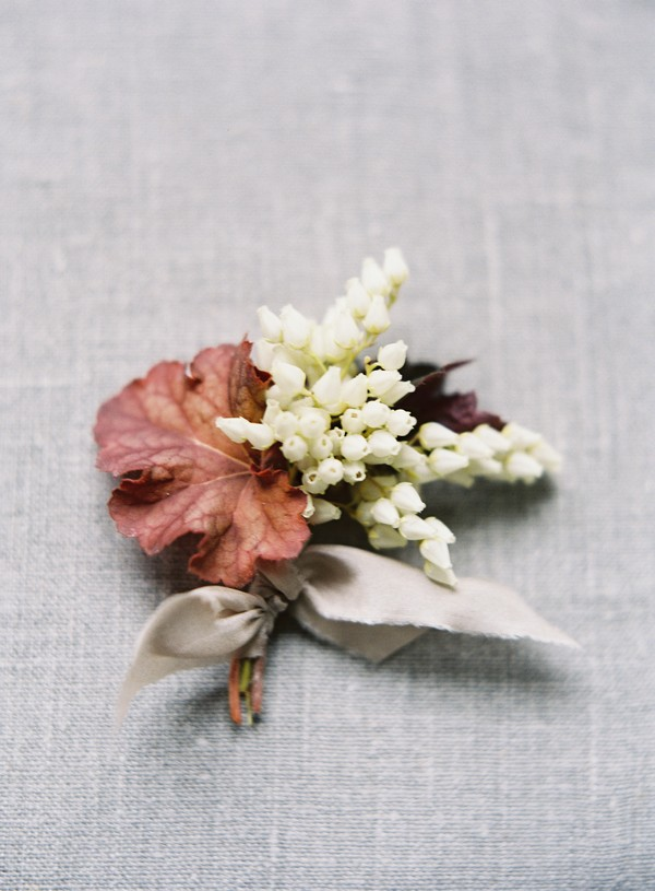 Buttonhole with red leaf and white heather flowers