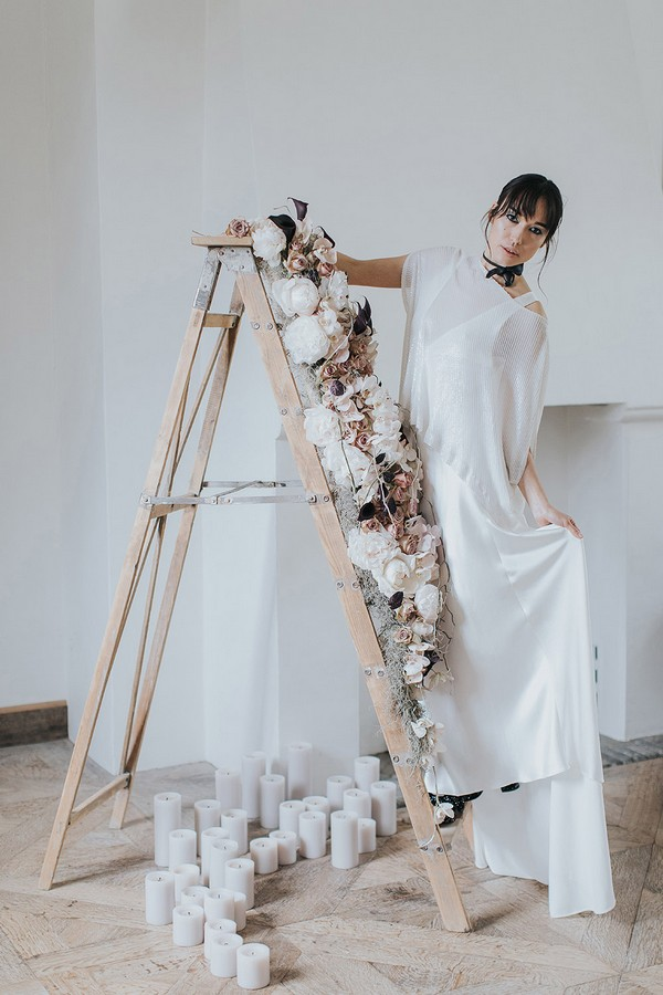 Bride standing on ladder covered in flowers
