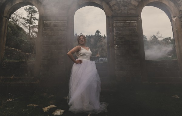 Bride by arch surrounded by smoke