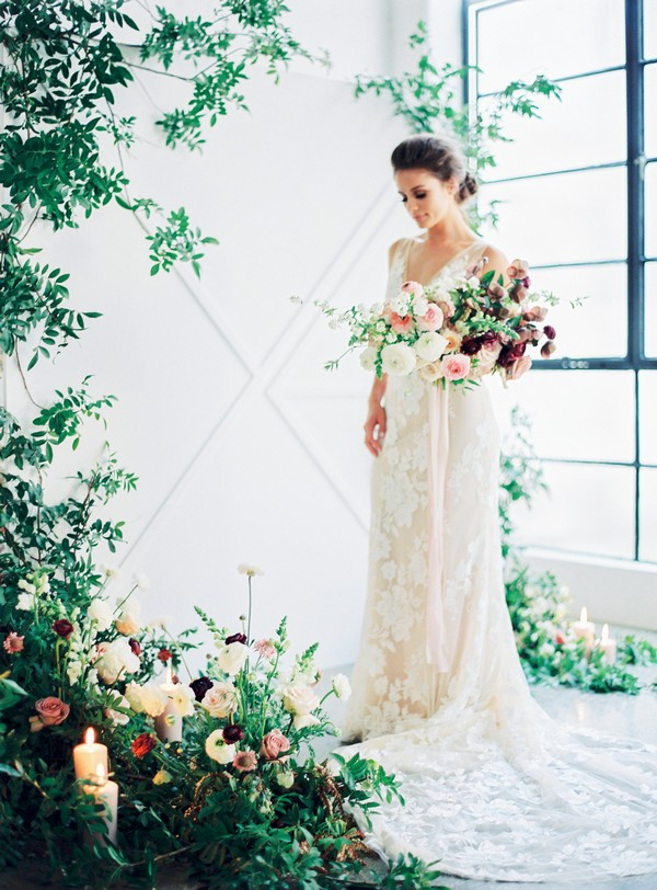 Bride holding bouquet in urban loft space