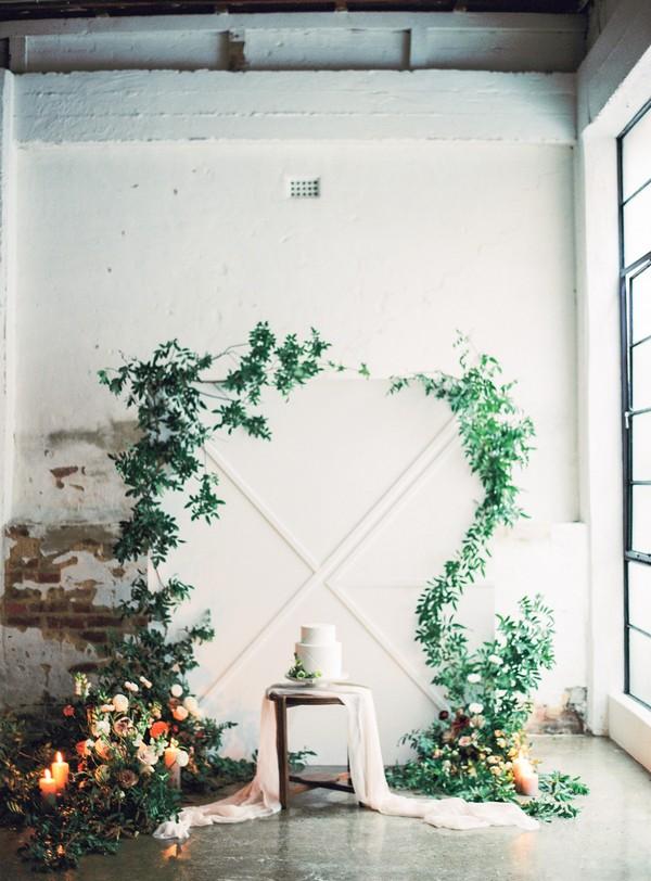 Plain white wedding cake in front of foliage backdrop
