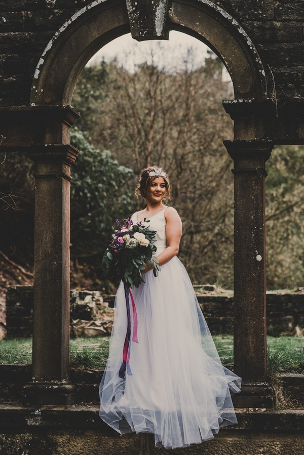 Bride holding bouquet standing by pillars
