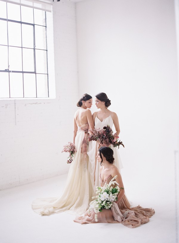 Three brides wearing blush and white dresses, holding bouquets