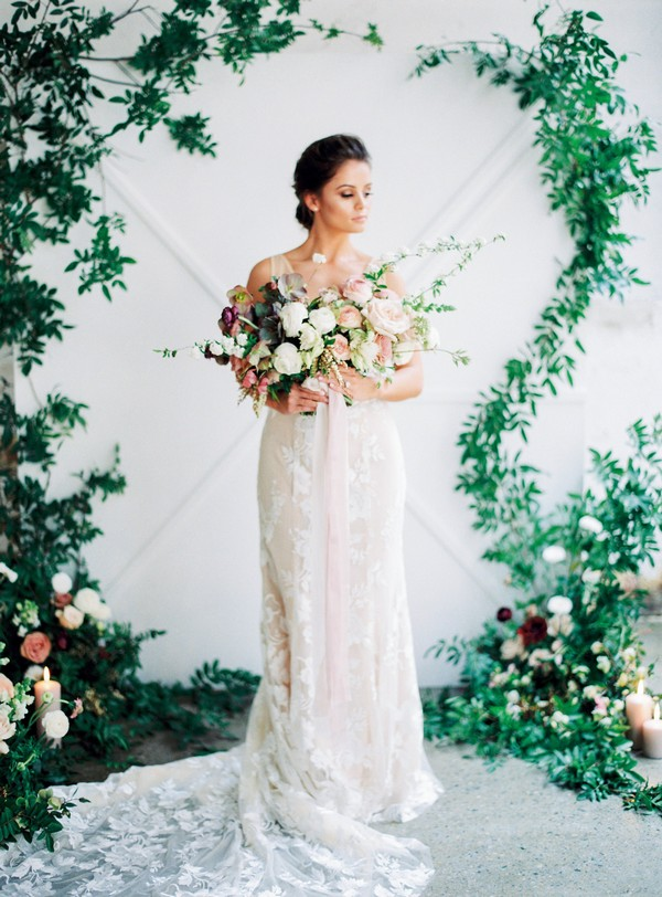Bride holding bouquet in front of foliage backdrop