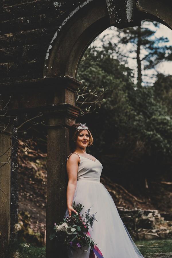 Bride leaning back on pillar