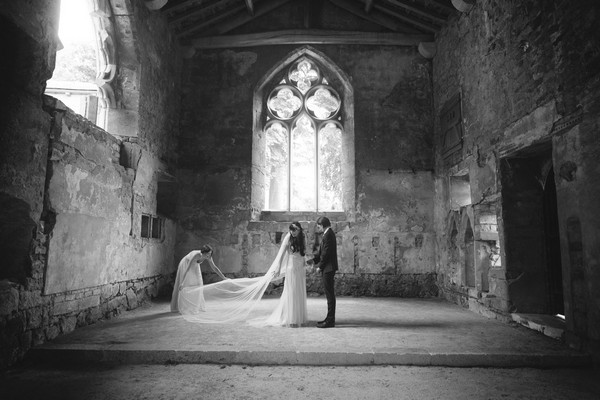 Bridesmaid pulling out bride's long veil - Picture by Bethany Lloyd-Clarke Photography