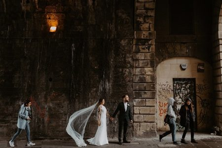 Bride and groom holding hands on path in urban area - Picture by The Hendrys Photography
