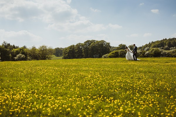 Bride and groom holding hands as they walk across a field of buttercups - Picture by Neil Jackson Photographic