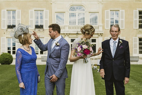 Groom straightening mother's hair as bride takes fluff off of father's jacket - Picture by York Place Studios