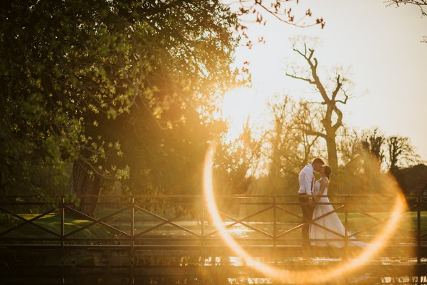 Picture of bride and groom kissing on bridge with glare of sun on lense - Picture by Lee Dann Photography