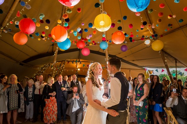 Bride and groom on dance floor under colourful lanterns - Picture by Heather Jackson Photography